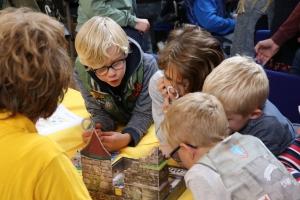 4 kinderen buige naar voren om een spel goed te zien.